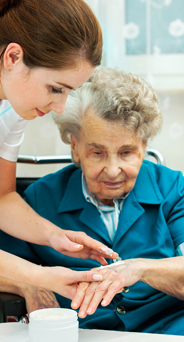caregiver checking senior woman's hand