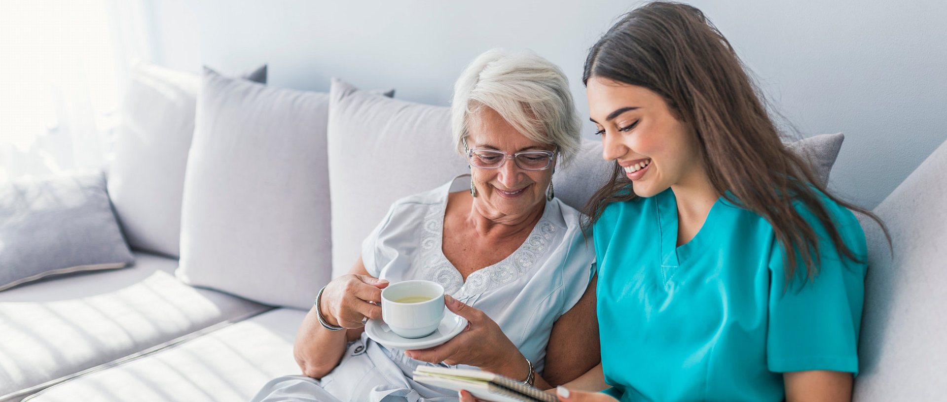 senior woman holding a cup of tea in bed with caregiver