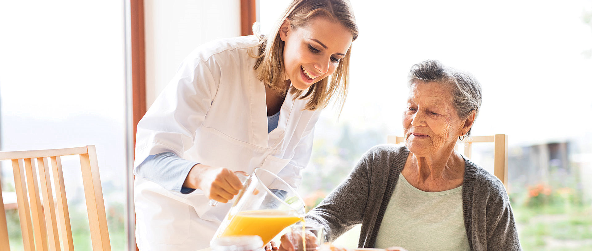 caregiver pouring juice on senior woman's glass