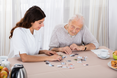 senior woman playing jigsaw puzzle with her caregiver